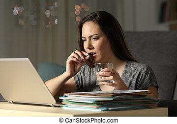 Entrepreneur working late hours taking painkiller pill