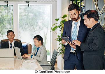 Entrepreneurs discussing document on tablet screen