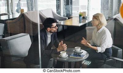 Entrepreneurs mature man and woman talking sitting at table...