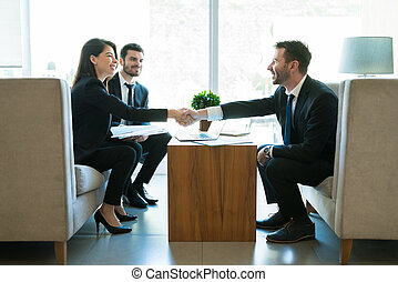 Entrepreneurs Sealing The Deal With Handshake In Hotel