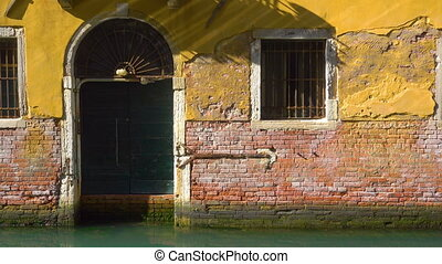Entry of old house by canal in Venice