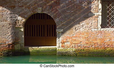 Entry of old house by canal in Venice and moving sun...
