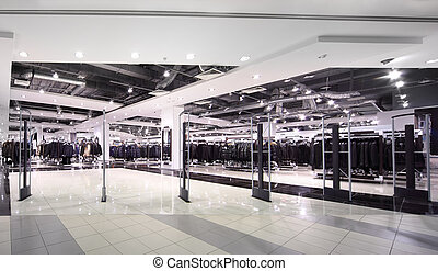 Entry to spacious lighting outerwear shop with many coat ...