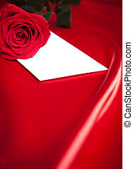 Envelope and red rose over silk background