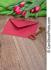Envelope, rusty key and tulip on a wooden background