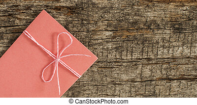 envelope tied with ribbon on wooden background