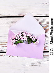 Envelope with flowers on wood.