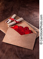 Envelope with lots of red hearts. Valentine's day. Brown wooden background.