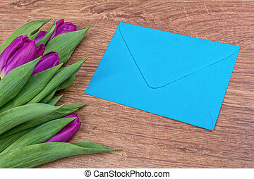Envelope with purple tulips on a wooden background