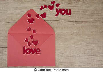 envelope with red paper hearts on wood background