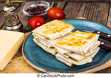 Envelopes of thin Armenian bread lavash fried with crispy crust. Filling of cheese, tomato and greens for hot breakfast