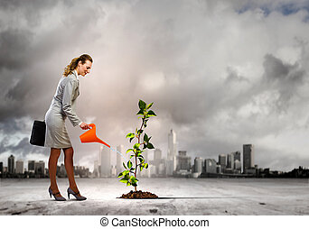 Environment protection - Image of businesswoman watering ...