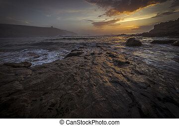 Environment, Sunset in Tagle beach. panoramic view of nice colorful huge cliff and sea on the back. Cantabria. Spain.