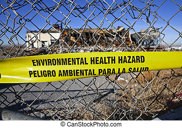 Environmental Health Hazard warning tape on a chain link...