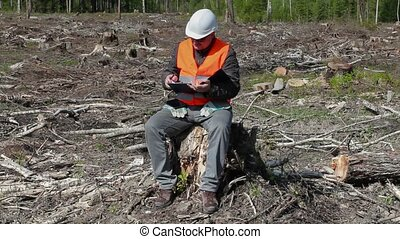 Environmental inspector writing in the destroyed forest