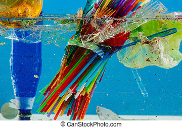 Colorful dangerous plastic straws placed under water with...