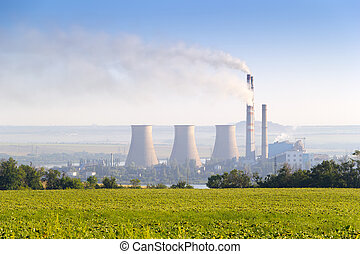 Environmental pollution concept. Pipes and towers of the thermoelectric plant. Green sunflowers field and tree planting in foreground.