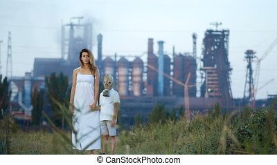 Environmental pollution, ecological disaster, nuclear war, post apocalypse concept. Care for future generations. Mom andchild in protective mask, face-guard to prevent breathing toxic air.
