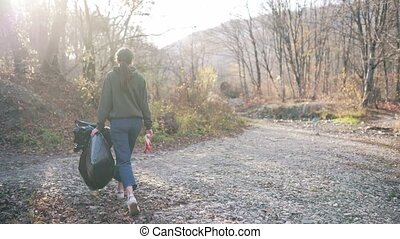 Environmental pollution, volunteering concept. A young woman with a black plastic bag and gloves in her hands walks on nature near the river 4k