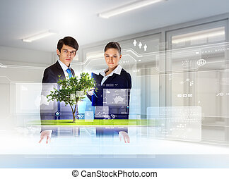 young businesspeople looking at high-tech image of tree