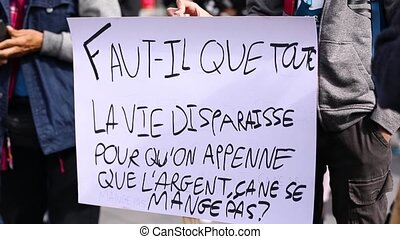 two close up shots of environmental slogans on hand written placards at a climate demonstration in french language