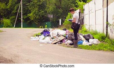 Environmentalist making photos of garbage dump. - Woman...