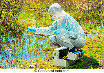 environmentalist on the shore of a forest lake takes water samples after an environmental disaster