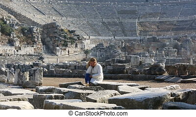 Ephesus Ancient City - very tired tourist resting on the...