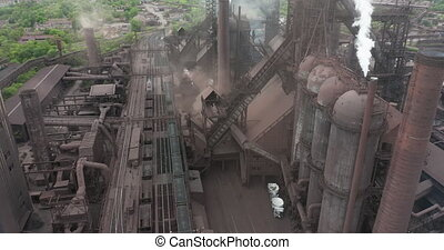 Epic aerial of pipes with white smoke emission. Plant pipes pollute atmosphere. Industrial factory pollution, smokestack exhaust gases. Industry zone, red and white pipes, thick smoke plumes
