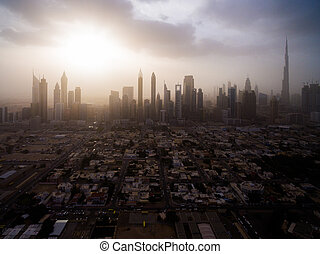 epic aerial view of the urban landscape, with large skyscrapers and the sun breaking through the clouds. Dubai, UAE