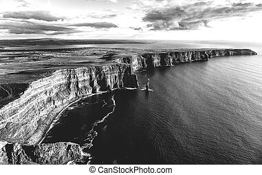 epic black and white photograph of the world famous cliffs of moher in county clare, ireland.
