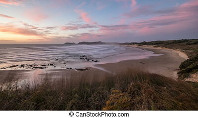 Peaceful evening with colorful sunset over ninety mile beach in New Zealand. Time lapse, Zoom in.