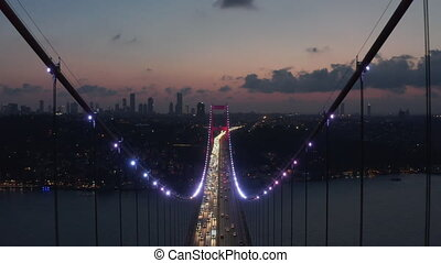 Epic Dolly forward through Istanbul Bosphorus Bridge Arch Illuminated in Red light at Night with Car traffic, Aerial Drone