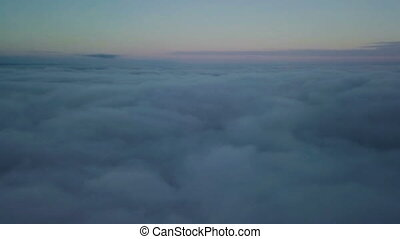 Epic flight down into the clouds at morning sunrise. Aerial slow motion drone shot