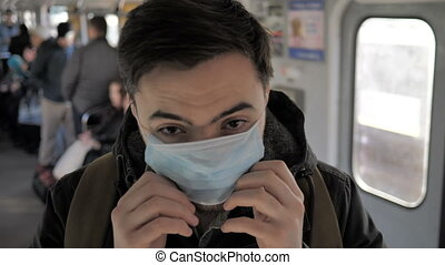 The young man with medical face mask stands in the crowdy flow metro subway virus coronavirus covid-19 infection epidemic