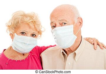 Senior couple wearing face masks to protect against swine flu epidemic.
