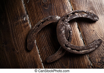 Equesrtian background. Lucky old horseshoes laying at wooden background.