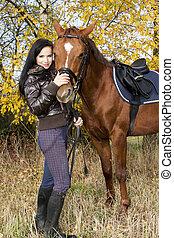 equestre, con, lei, cavallo, in, autunnale, natura