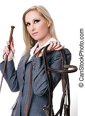 Equestrian rider holding bridal and horsewhip.