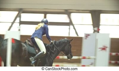 Equestrian rider on the stallion jumping throw the barrier...