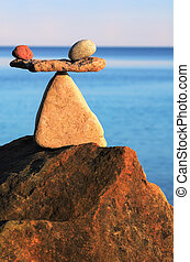 Equilibrium - Symbol of scales on the top of boulder