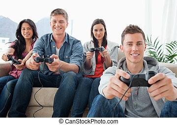 equipaggi, gruppo, divano, sedere insieme, uno, sguardo, mentre, macchina fotografica, giochi, essi, sorridente, sedere, amici, gioco, suolo