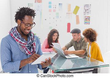 equipe, criativo, usando, trabalhando, sorrindo, tabuleta, atrás de, homem