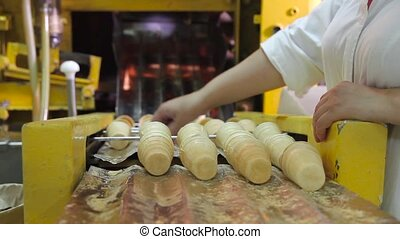 Equipment for baking waffle cups in an ice cream factory. The worker sorts the finished wafer cups and collects them in a pile. Production of wafer cups for ice cream.