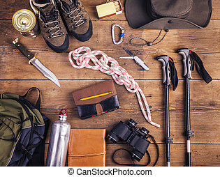 Equipment for hiking on a wooden floor background
