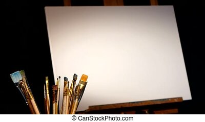 Equipment for painting, rotation wooden easel and the blank canvas on it, lot of brushes isolated, black background