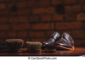 equipment for shoe shining against the brick wall - three...