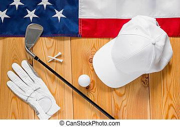 equipo, para, golf, y, un, bandera estadounidense, en, un, piso de madera, vista desde arriba