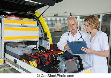 equipo, paramédicos, verificar, engranaje, en, un, ambulancia