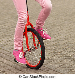 Equipoise - Balancing girl driving an unicycle on the...
